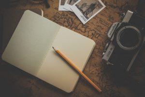 Notizbuch mit Bleistift und Kamera